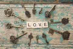 Round frame of antique keys with love inscription on old painted Stock Image