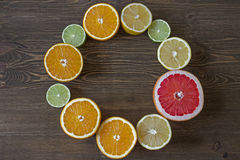 Round frame with citrus fruits on wooden background. Round frame with citrus fruits on grey wooden background Royalty Free Stock Photos