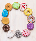 Round frame of colorful doughnuts on white wooden background, top view. Round frame of colorful doughnuts white wooden background, top view royalty free stock images