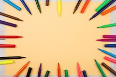 Round frame from colorful felt-tip pens, yellow paper. Round frame from colorful felt-tip pens and yellow paper royalty free stock photos