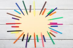 Round frame from colorful felt-tip pens and yellow paper. On wooden table royalty free stock photo