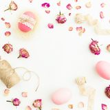 Round frame of Easter pink eggs with twine, roses flowers and tapes on white background, Top view, Fat lay. Easter holiday Royalty Free Stock Photos