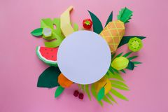 Exotic fruits made of paper. Handmade paper art. Round frame with exotic fruits with different tropical leaves made of paper on pink background royalty free stock photo