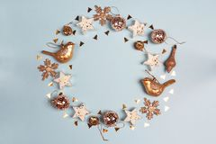 Round frame of golden Christmas decorations wit copy space on blue background.