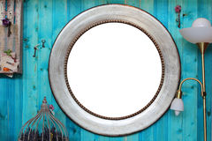 Round Frame in the Interior. Vintage round metallized frame on wooden wall with embellishments and interior items stock image