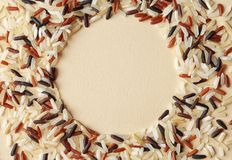 Round frame made with mixed brown and other types of rice on color background, top view. Space for text royalty free stock photography
