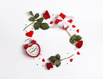 Round frame made of rose flowers, gifts, alarm clock and decorative hearts on white background. St. Valentines day background. Copy space, flat lay, top down stock photography