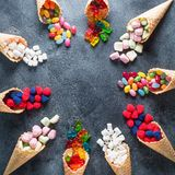Round Frame Of Colorful Bright Assorted Candy In Waffle Cones On Dark Background. Flat Lay, Top View Royalty Free Stock Photos
