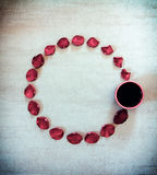 Round frame of petals of scarlet rose and cup of coffee on gray grunge background with vignette with space for text royalty free stock image