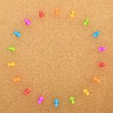 Round frame of pins over cork board Royalty Free Stock Images