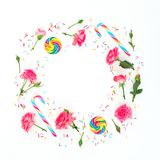 Round frame of rose flowers with petals and bright sugar candy on white background. Flat lay, top view. stock images