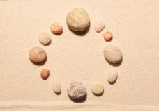 Round frame of sea stones on sand. Summer beach background Royalty Free Stock Photo