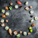 Round frame of set of Japanese food on dark background. Sushi rolls, nigiri, salmon steak, rice and avocado. Flat lay. Top view. Round frame of set of Japanese royalty free stock photography