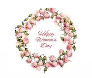 Round frame of small pink roses with Women`s Day greeting messag. On white background. Flat lay, top view royalty free stock image