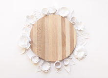 Round frame with white paper flowers. And cutting board on white background. Cut from paper. Place for your text Royalty Free Stock Photo