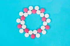 Round frame of white and red pills on light blue background stock images