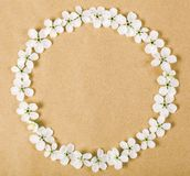 Round frame wreath made of white spring flowers on brown paper background. Top view. Flat lay royalty free stock photography