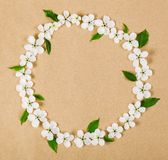 Round frame wreath made of white spring flowers and green leaves on brown paper background. Flat lay. Round frame wreath made of white spring flowers and green stock images