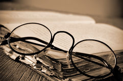 Round-framed eyeglasses and old book, in sepia toning Stock Photography