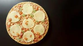 Round frozen pizza. Tomatoes, mozzarella, pesto, basil. Anthracite background. Stock Image