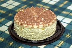 Round gąbka tort na zielonym w kratkę tablecloth na stole Obraz Stock