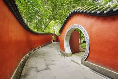 Round gate in red wall passage surrounded by bamboo forest. Round gate in red wall passage surrounded by bamboo forest, Wuhou Temple, Chengdu, China Royalty Free Stock Photography