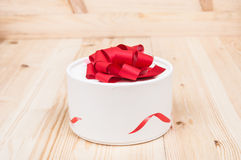 Round gift box closeup. On wooden background stock images