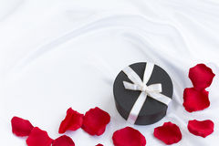 Round gift box with white ribbon. Gift box with white ribbon with rose pettals Stock Photos
