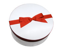 Round gift red labeled. A white and round gift box with a red ribbon, isolated against a white background Stock Photos