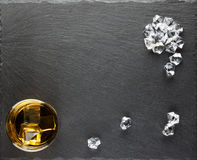 Round glass of whiskey and ice cubes scattered Stock Image