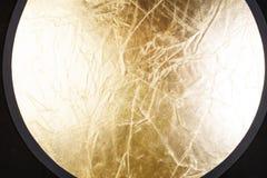 Golden photo reflector on black background Royalty Free Stock Photo