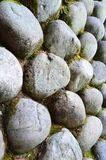 Side view of round granite stone wall with green moss stock photography