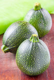 Round green zucchini on wooden table Royalty Free Stock Photography