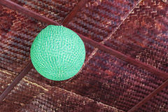 Round green lamp with bamboo weave. Low angle view Round lamp is made of green thread, beautifully weaved hanging on bamboo weave ceiling Royalty Free Stock Images