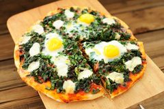 Round green pizza with eggs and mozarella on wooden board Royalty Free Stock Image