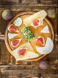 Round gutting board with cheese and figs. Top view Stock Photo