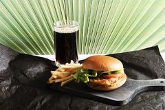 Round hamburger with chicken cutlet and French fries and a glass. Of coke on a dark wooden Board Stock Photography