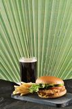 Round hamburger with chicken cutlet and French fries and a glass. Of coke on a dark wooden Board Royalty Free Stock Photography