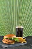Round hamburger with chicken cutlet and French fries and a glass. Of coke on a dark wooden Board Stock Photo