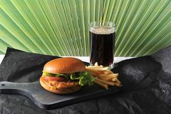 Round hamburger with chicken cutlet and French fries and a glass. Of coke on a dark wooden Board Stock Image