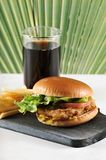 Round hamburger with chicken cutlet and French fries and a glass. Of coke on a dark wooden Board Royalty Free Stock Image