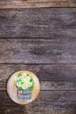 Round handpainted gingerbread on wooden background. Bouquet of daisies in a basket. Flat lay. Copy space. Sweet dessert as a gift stock photography