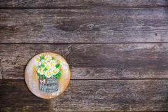 Round handpainted gingerbread on wooden background. Bouquet of daisies in a basket. Flat lay. Copy space. Sweet dessert as a gift stock photo
