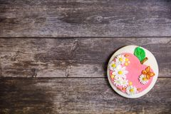 Round handpainted gingerbread on wooden background. Flat lay. Apple with flowers and butterflies. Copy space. Sweet dessert as a stock images