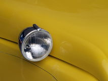 Round head light on yellow car. With antique retro look and curves lines Stock Photo