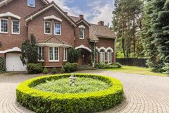 Round hedge and a small statue in the middle of a cobblestone dr. Iveway to an elegant, english style house with white windows and brick exterior royalty free stock photos