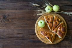 Round home-made apple pie, cobbler, brown Betty, Apple Charlotte. On wooden background with apples and spikelets stock photos