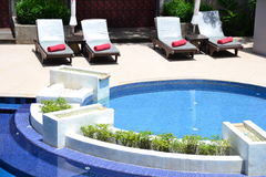 Round hotel swimming pool. With lounge chairs Stock Images