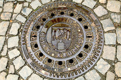 Round Iron Sewer Manhole Cover. Iron Round Sewer Manhole Cover on the pavement in the Czech town of Krumlov Stock Photos