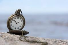 Round kieszeniowy zegarek na kamieniu przeciw niebu z chmurami, tarcza, Fotografia Royalty Free